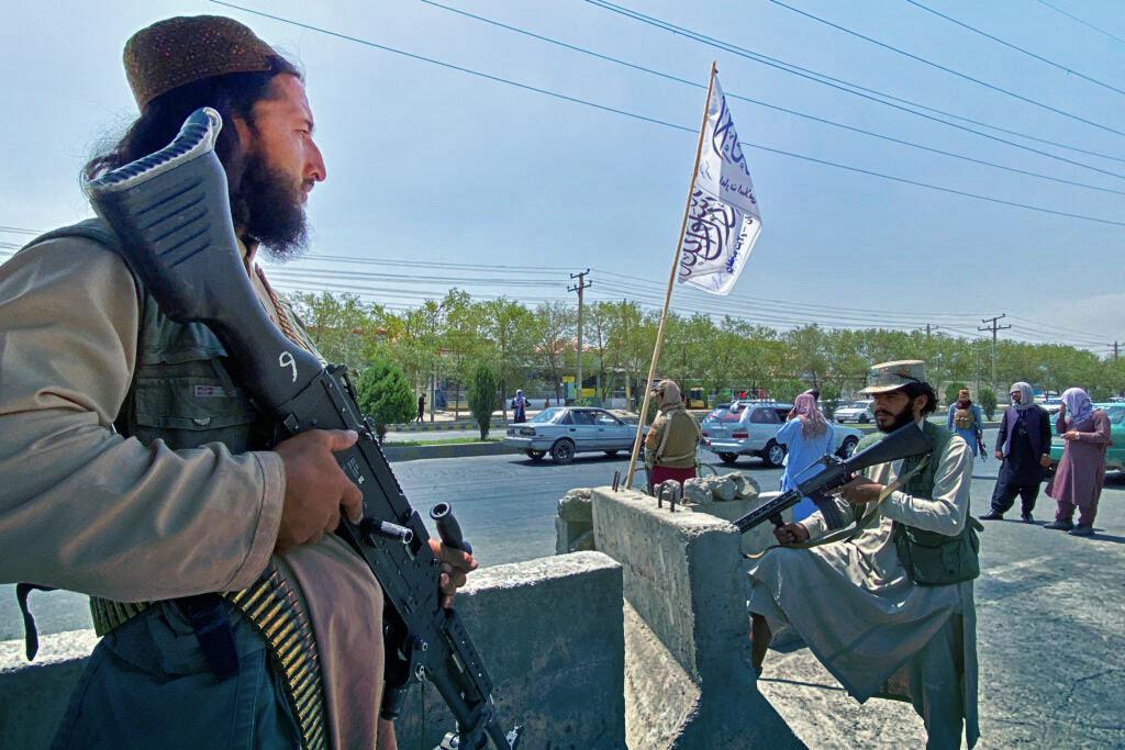 Pejuang Taliban berjaga di pintu masuk di luar Kementerian Dalam Negeri di Kabul pada 17 Agustus 2021. (Foto oleh Javed Tanveer / AFP via Getty Images)